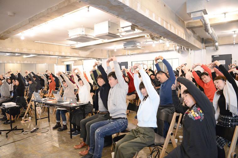 【写真】腕を伸ばしてストレッチをする参加者ら