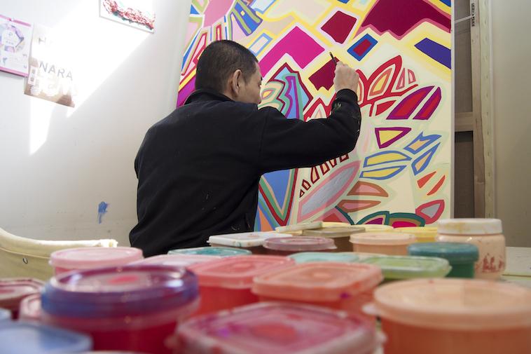【写真】机に並べられたたくさんの絵の具の奥で、キャンバスに絵を描くやまのまさしさん