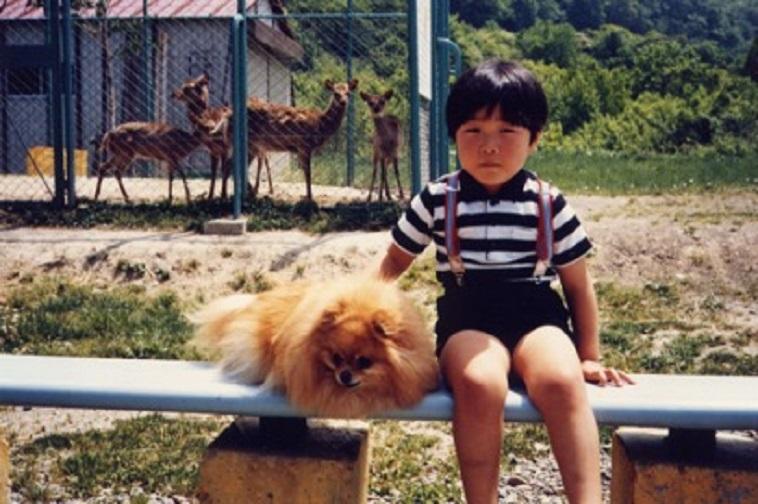 【写真】こばやしりょうこさんの息子さんの幼少期の頃の写真。犬と一緒に写っており、後ろには子鹿が3頭いる。