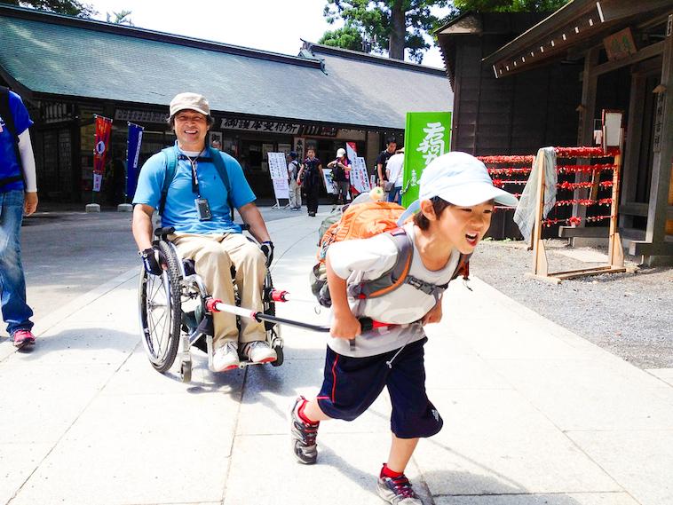 【写真】JINRIKIを使って大人の乗った車椅子を引っ張る少年