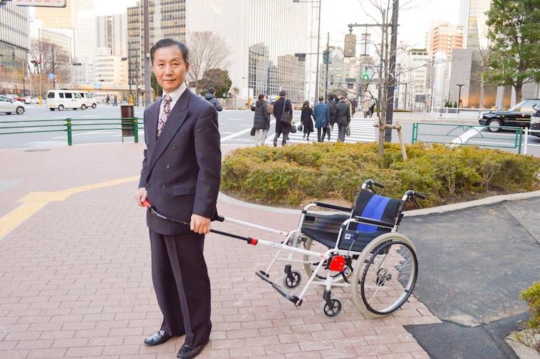 【写真】歩道でJINRIKIを取り付けた車椅子を持つ株式会社JINRIKIのなかむら社長
