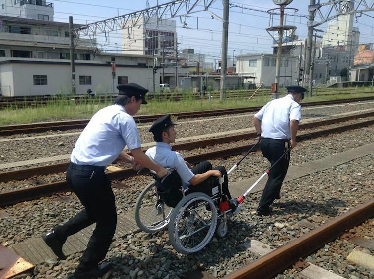 【写真】砂利の多い線路の上を、JINRIKIをつけた車椅子で移動訓練をする運転士たち
