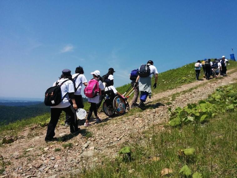 【写真】JINRIKIを使って、砂利の多い山道を登る車椅子利用者