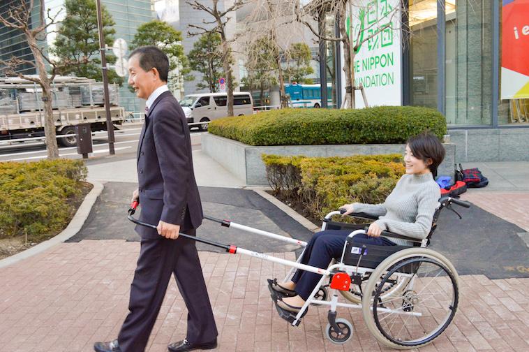 【写真】インタビュー当日、JINRIKIを取り付けた車椅子に乗るインタビュアーと、JINRIKIを引っ張る社長のなかむらさん
