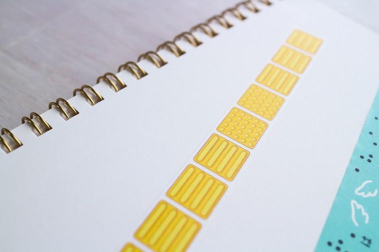 【写真】ノートにはられた点字ブロックのマスキングテープ