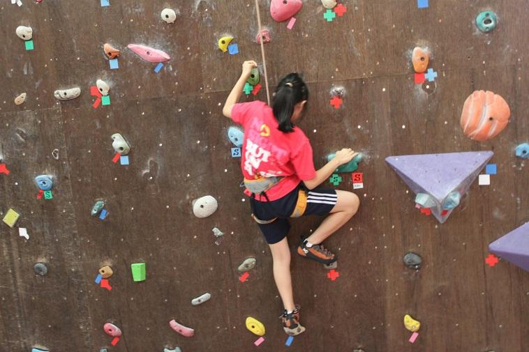 【写真】つばさの会のイベントの一つである、ロッククライミング教室でクライミングをする女の子