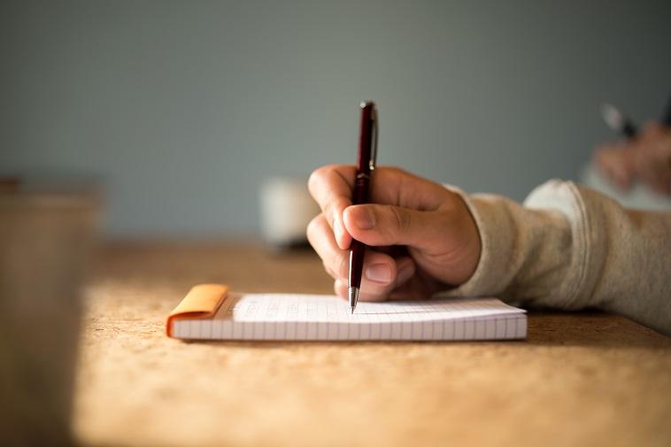 【写真】紙とペンでメモを取るおおたなおきさん
