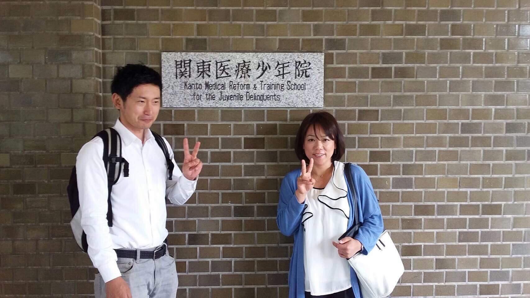 【写真】関東医療少年院の建物前で微笑むつとみひろしさん、なかむらすえこさん
