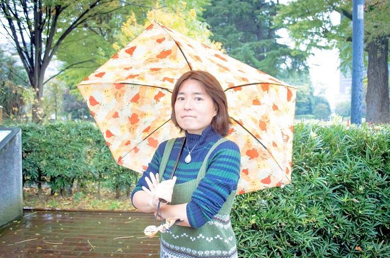 【写真】傘をさしてカメラに目線を向けるそでやまさん