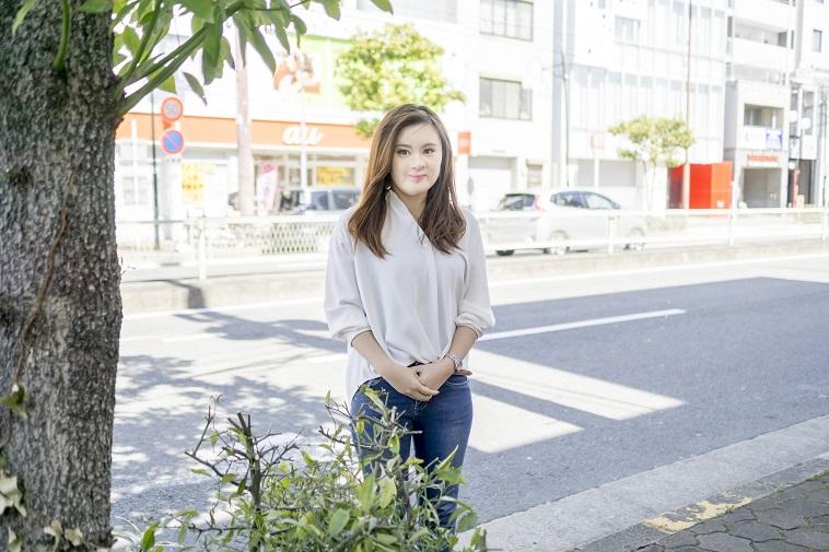 【写真】笑みを浮かべながら、木の隣に立つこばやしさん