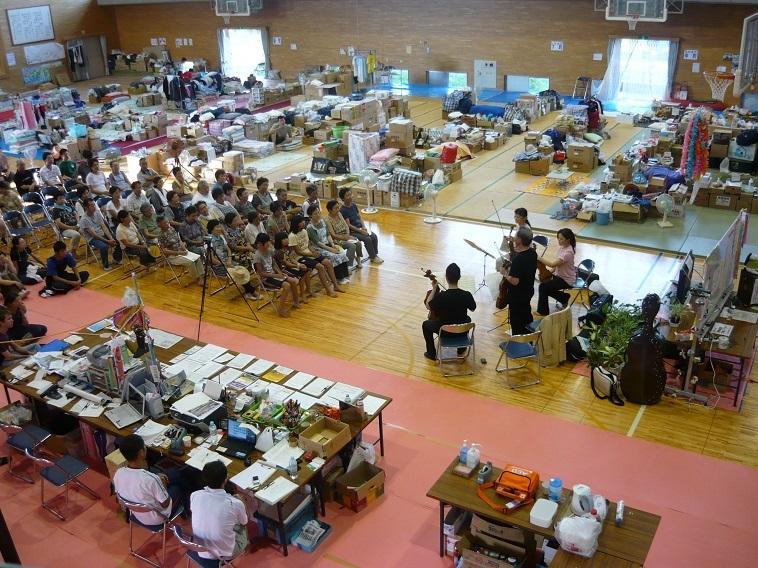 【写真】被災地の体育館でワークショップを行う日本フィルのメンバーと聞き入る被災者