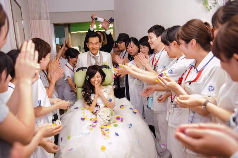 【写真】病院のスタッフに拍手をされながら迎えられるウェディング姿の新郎と車椅子の花嫁