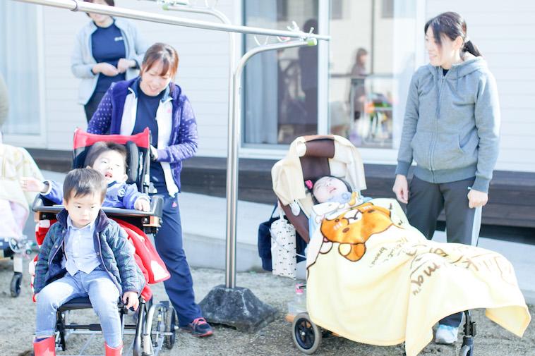 【写真】青天の下子供たちはベビーカーに乗ってスタッフが付き添い外に出ます