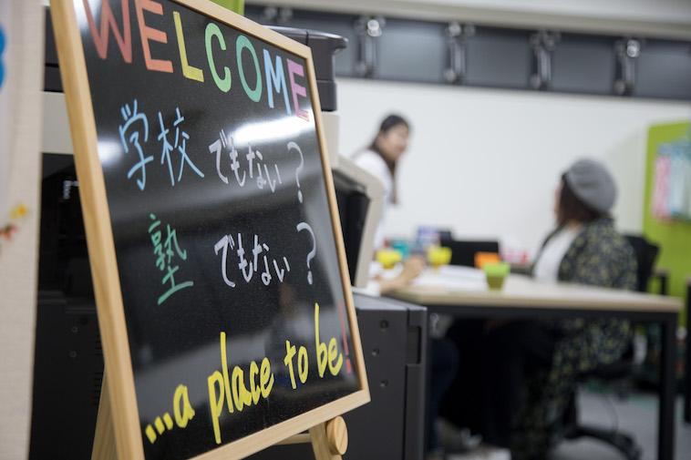 【写真】ウェルカムと書かれた看板には「学校でもない?塾でもない?…a place to be」と書かれている