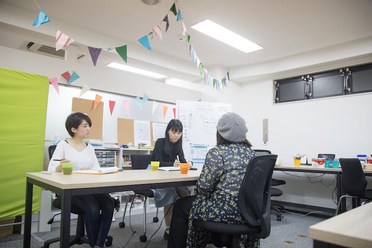 【写真】インタビューをした部屋にはカラフルな旗が飾られ明るい雰囲気