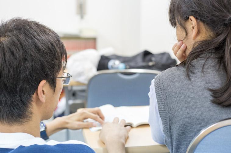 【写真】スタッフが生徒の横に座り、一緒に学習に取り組んでいる
