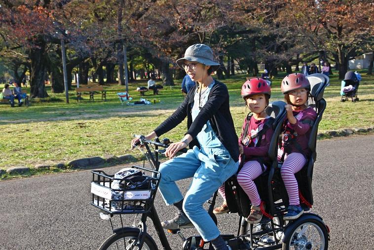 【写真】ふたごじてんしゃに二人の子供を乗せて体験するお母さん