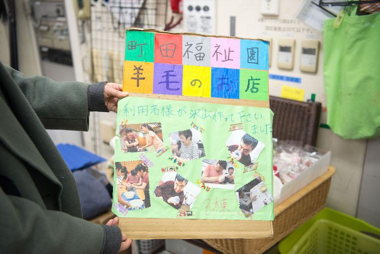 【写真】町田福祉園羊毛のお店の看板。手作りで、利用者さんの写真がたくさん貼られている