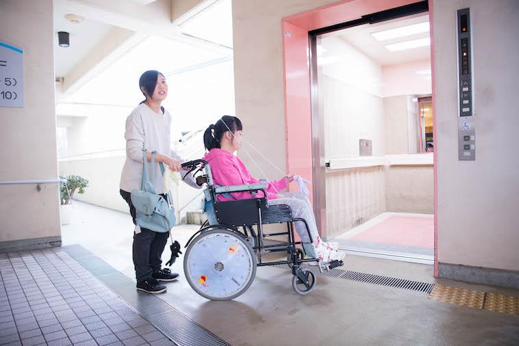 【写真】利用者さんの乗った車椅子を押すかなせさん