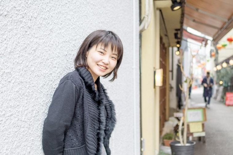 【写真】壁の前で笑顔で立っているこんどうあきさん