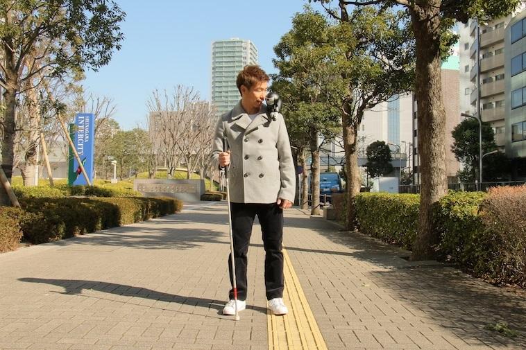 【写真】ニンニンを肩に乗せ、道案内を聞く視覚障害の男性