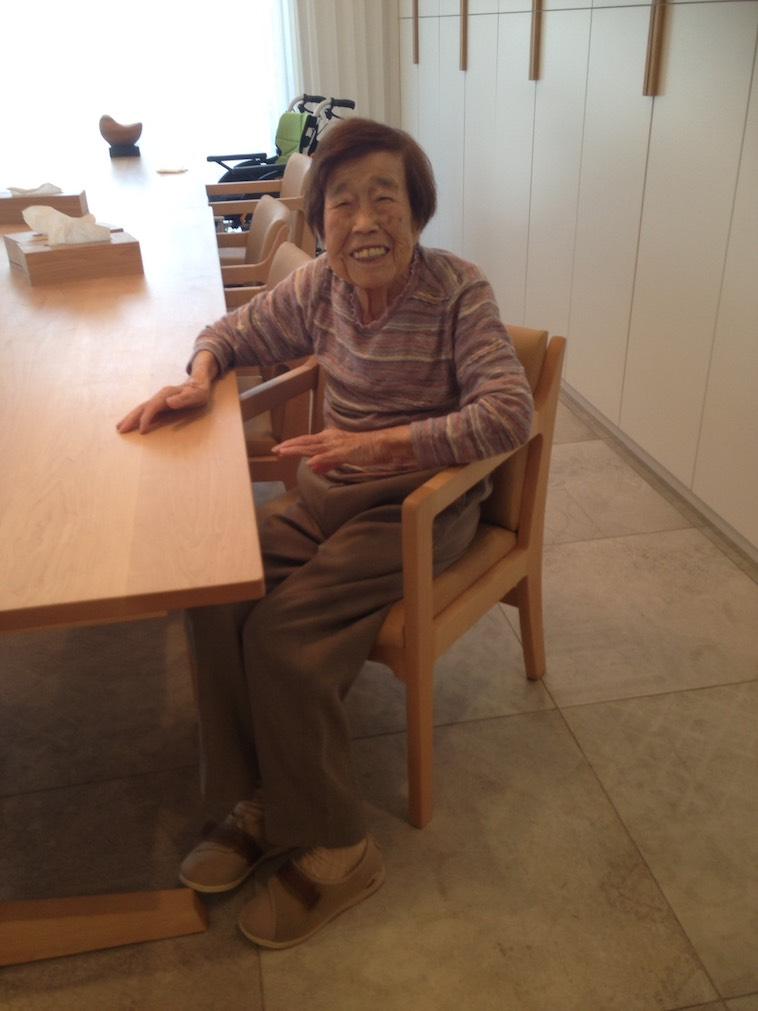 【写真】椅子に座りながら笑顔でこちらを見つめる入居者。