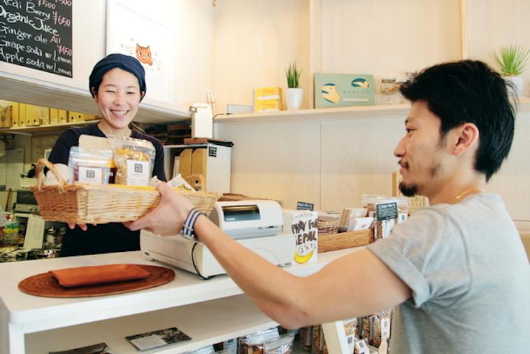 【写真】お店でお客さんにグラノーラを渡す笑顔のスタッフ