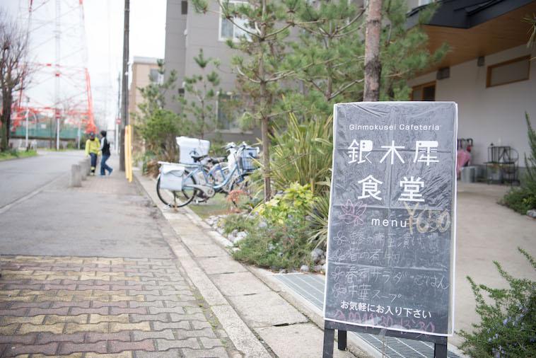 ぎんもくせいの建物の前。ぎんもくせい食堂の看板が置いてある。