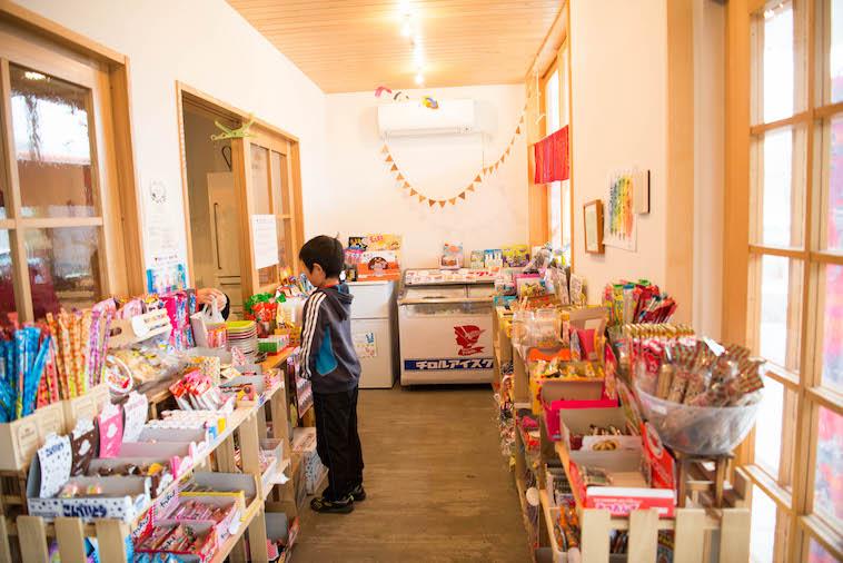 【写真】ぎんもくせいに併設されている駄菓子屋。近所のこどもが1人お菓子を眺めている。