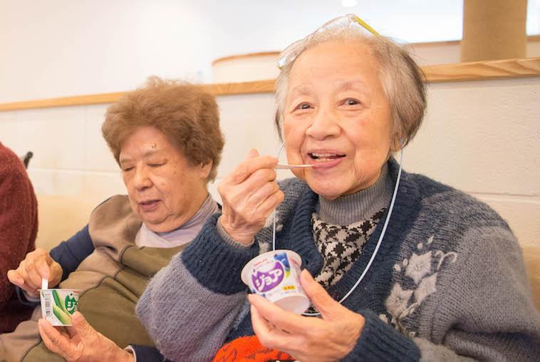 【写真】ヨーグルトを嬉しそうに食べる入居者。