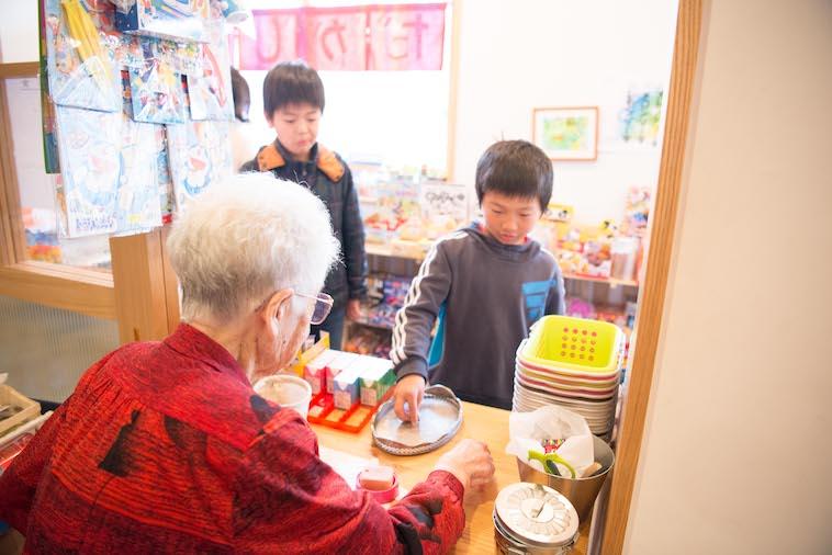 【写真】店番をしている入居者にお金を渡すこども 。入居者とこどもの交流が生まれている。