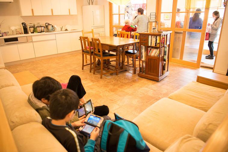 【写真】ぎんもくせいのリビング。こどもたちがくつろぎながらゲーム機で遊んでいる。