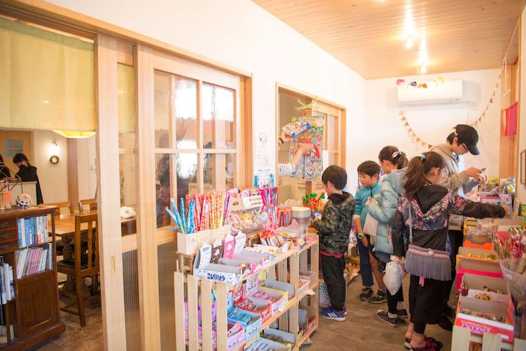 【写真】ぎんもくせいの駄菓子屋。複数のこどもたちが、お菓子を持って店番の入居者の前に並んでいる。