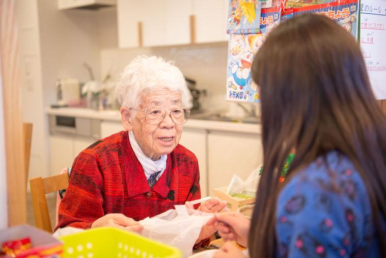 【写真】店番をしている入居者のしきもりさん。ほのかに笑みを浮かべている。