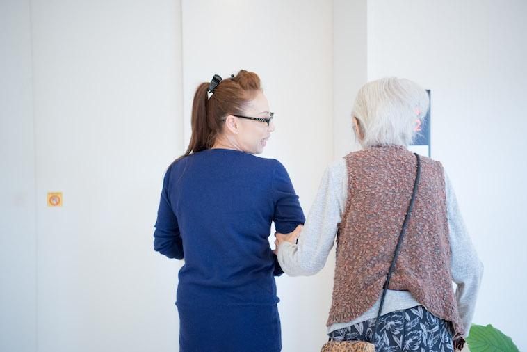 【写真】入居者がれいこさんの腕を掴みながら、楽しそうに一緒に歩いている。