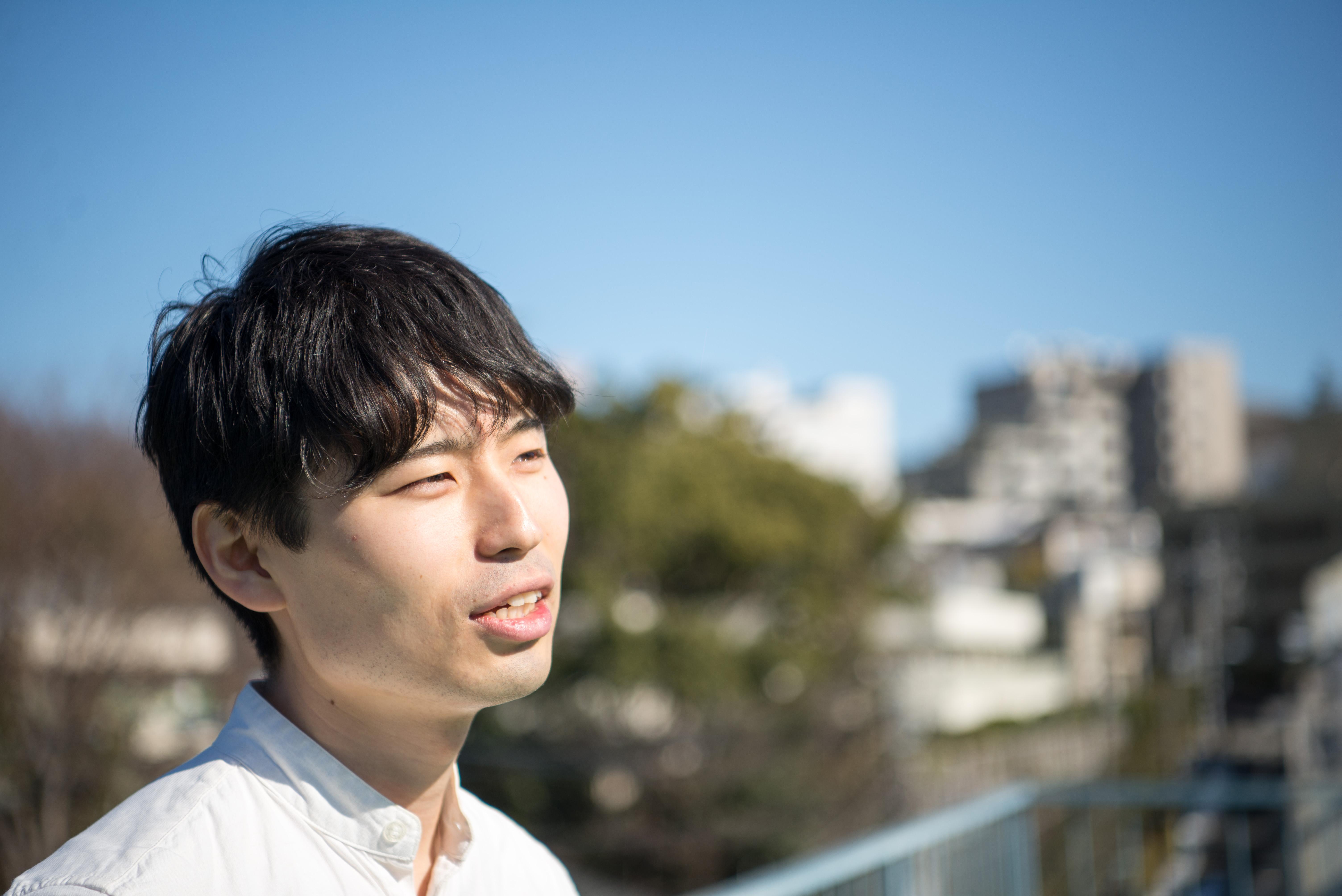 【写真】青空を背景に、微笑みながら語るくさかりさん