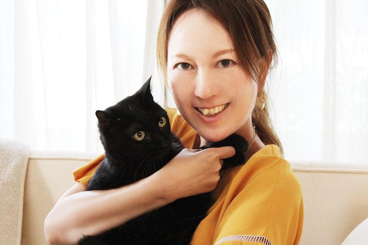 【写真】黒猫を抱いて微笑むセリさん