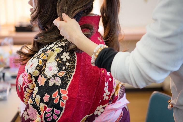 【写真】振袖姿の女性の髪型を整える様子