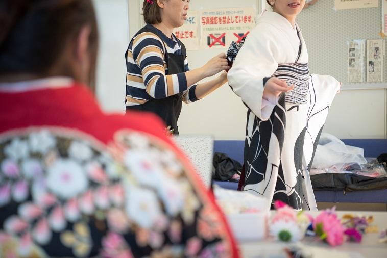 【写真】振袖姿の女性が、帯を整えてもらう様子