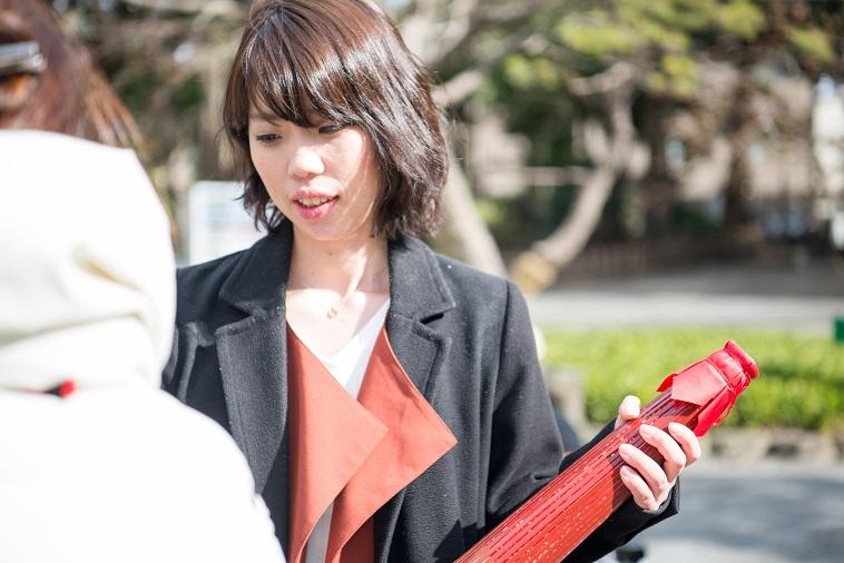 【写真】和傘をもち、振袖姿の女性と話すまさこさん