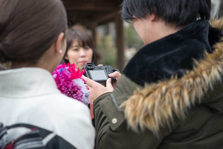 【写真】撮影された写真を確認する振袖姿の女性と、その様子を眺めるまさこさん