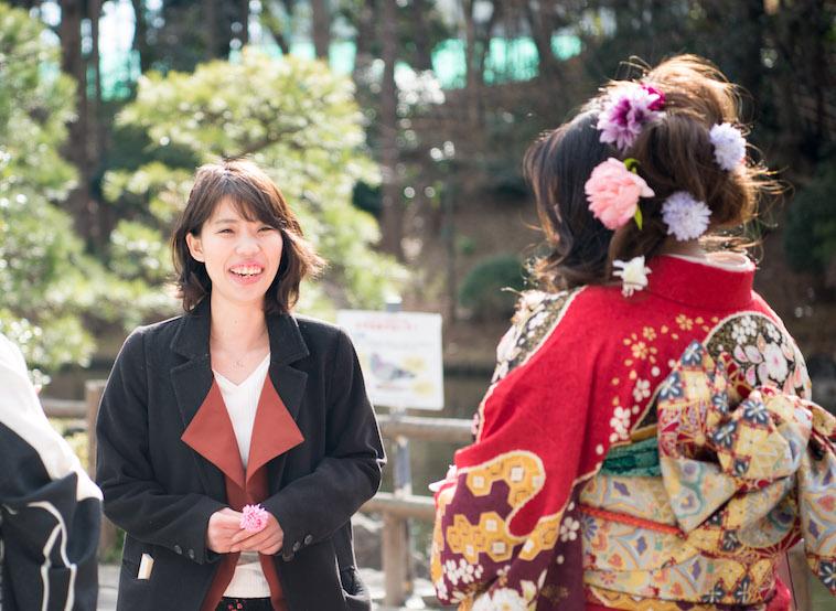 【写真】振袖を着た女性を眩しそうな笑顔で眺めるまさこさん