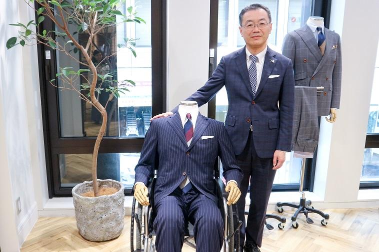 【写真】オーダースーツと並ぶ花菱代表取締役の、のなかまさひこさん