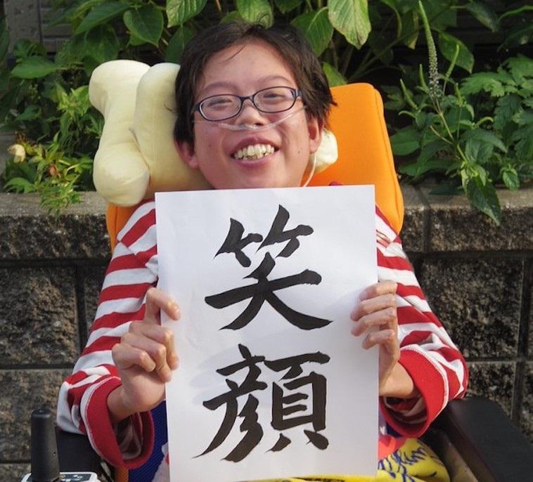 【写真】笑顔という紙を掲げて微笑む車椅子の子ども