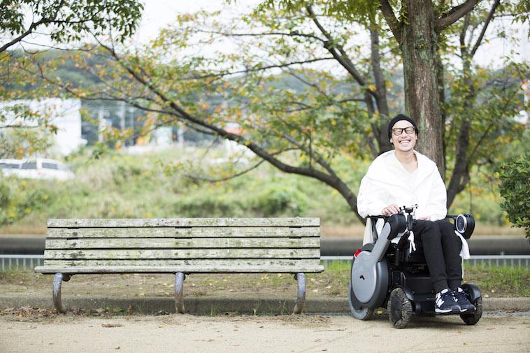 【写真】木の前で車椅子に座り笑顔のおちみずようすけさん