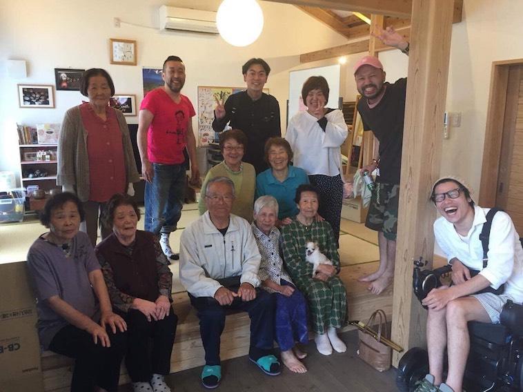 【写真】笑顔のおちあいさんと、熊本で出会った方々の写真。みなさん笑顔でほほえんでいて和やかな雰囲気が流れている。