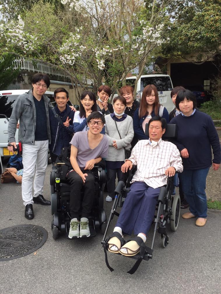 【写真】車椅子に座る笑顔のおちみずようすけさんとなかのげんぞうさん。周りをスタッフの方が楽しそうに囲んでいる。