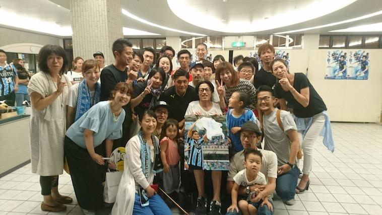 【写真】サッカー日本代表のおおくぼ選手とおちみずようすけさん。楽しそうな表情の大勢の人々が二人を囲んでいる。