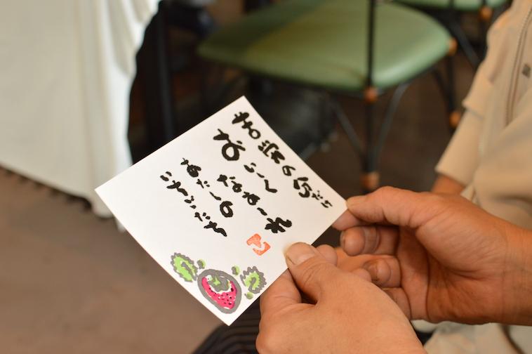 【写真】しみずさんの書のアップ。書には「苦労の分だけおいしくなあれ。わたしのいちごたち」という言葉と、いちごのイラストが描かれている。