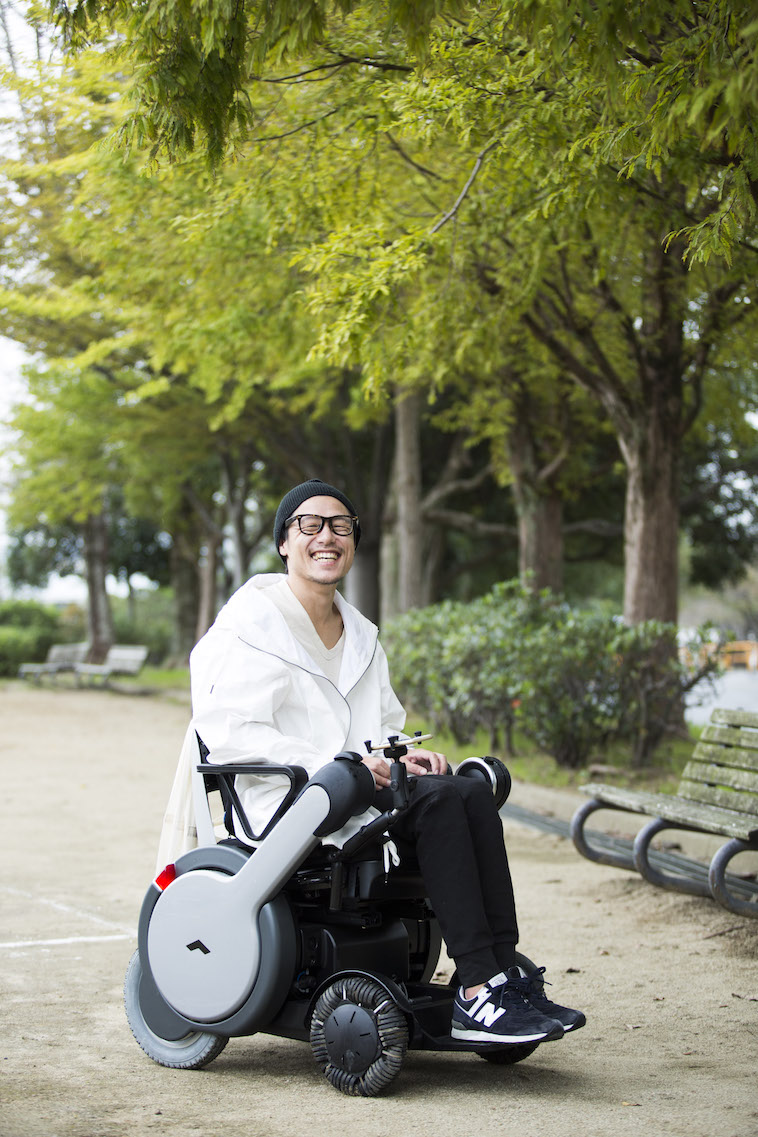 【写真】木々の前で、満開の笑顔をみせて車椅子に座るおちあいさん